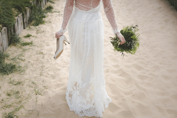 woman in wedding dress on the beach holding a bouquet and heels